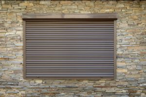 A window with brown metal rolling shutters. Wall decoration with artificial flatten stone