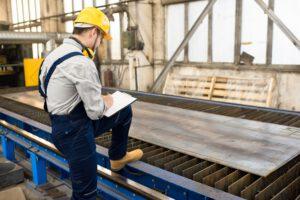 Engineer analyzing quality of metal sheet