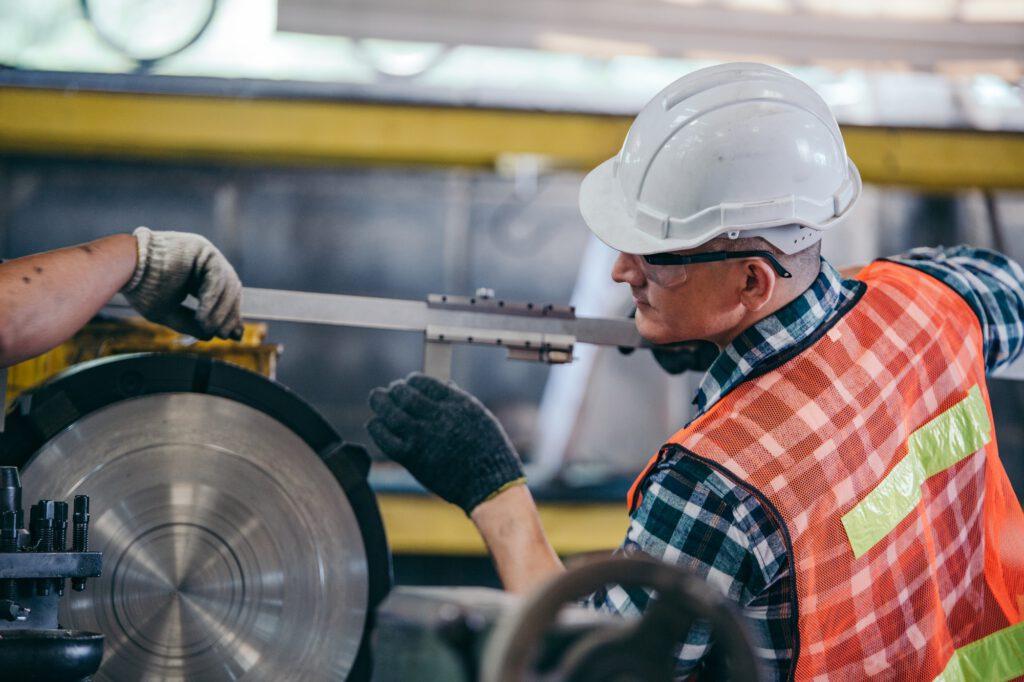 Engineer metalworker working on lathe machine